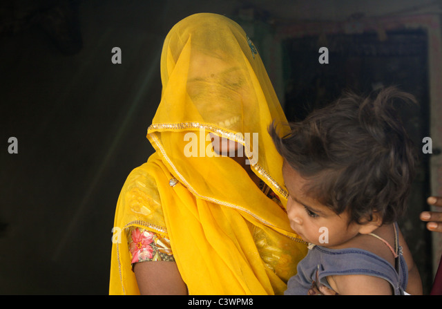 A tribal woman dressed in traditional clothes holding her child in Udaipur, Rajasthan, India - Stock Image