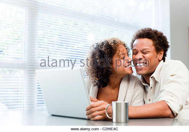 Smiling couple using laptop together - Stock-Bilder