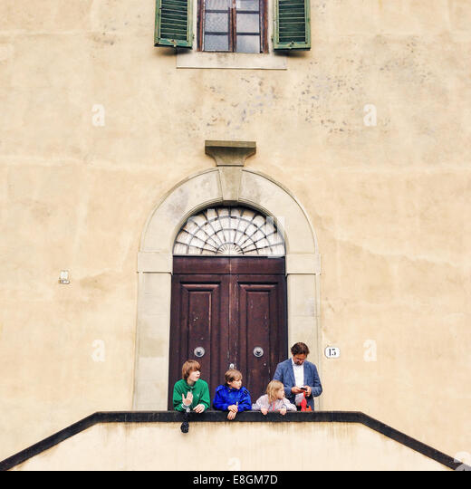 Italy, Florence, Father with three kids (10-11, 12-13) standing in front of building - Stock-Bilder