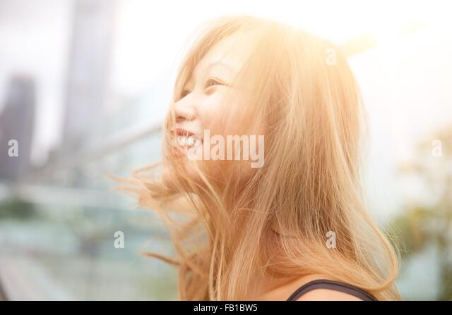Portrait of young woman outdoors, laughing, close-up - Stock Image