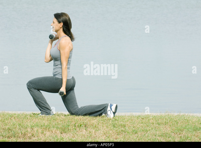 Woman working out by edge of water - Stock Image