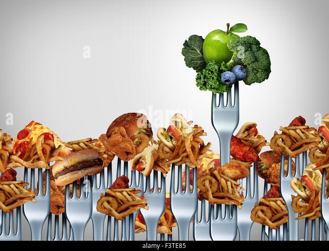 Fruit and vegetable choice concept and nutrition choices symbol as a group of dinner fork icons with junk food. - Stock Image