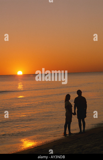 Beach Romantic couple sunset holding hands - Stock Image