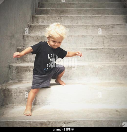 boy walking down steps - Stock-Bilder