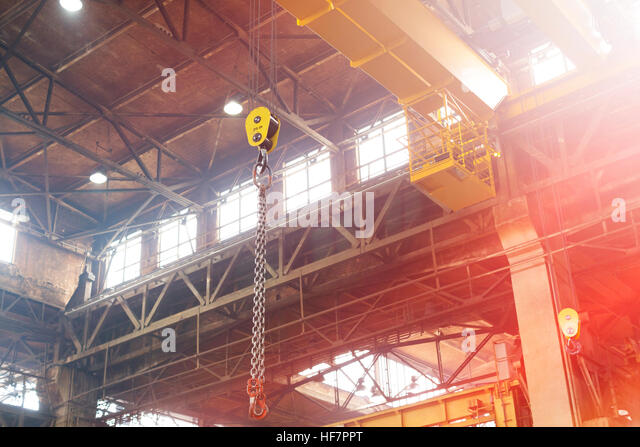 Chain hanging from crane in steel factory - Stock Image