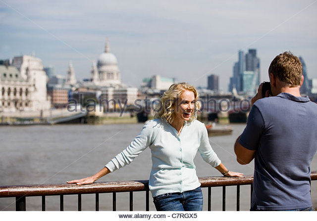 A middle-aged man taking a photograph of his partner next to the river Thames - Stock Image