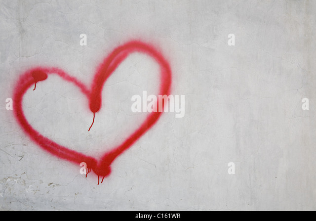 Red heart shape on white wall - Stock Image