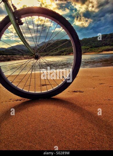Bike wheel on the beach - Stock Image