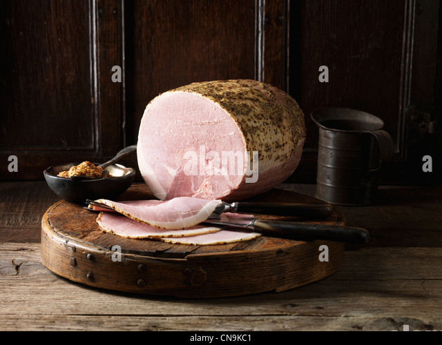 Sliced ham on wooden board - Stock Image