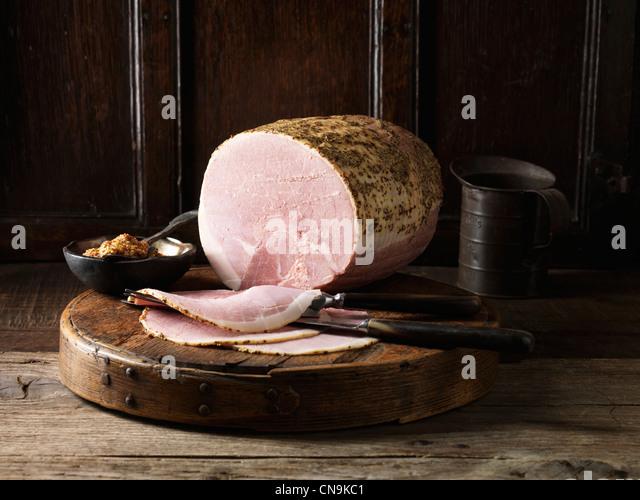Sliced ham on wooden board - Stock Image