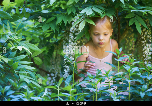 Girl in ballet costume playing in bush - Stock Image