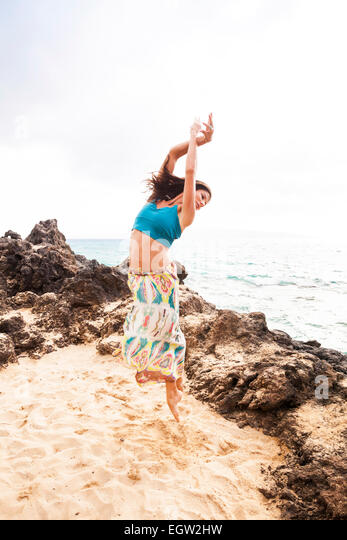 Woman dancing and jumping on beach. - Stock Image