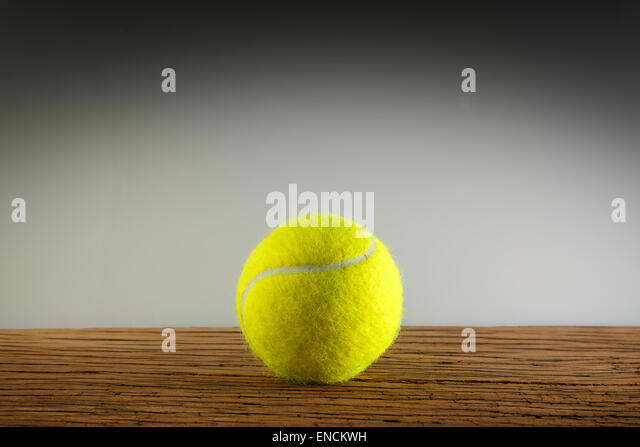 New yellow tennis balls on a wooden table. In light and shadow. Copy space room text. - Stock Image