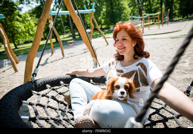 Mature woman swinging with her animal friend outside in playground - Stock Image