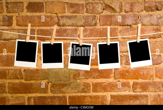Instant transfer images or Polaroids on a clothesline in front of a brick wall with clipping paths for images area - Stock Image