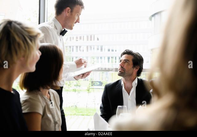 Waiter taking businessmans order - Stock Image