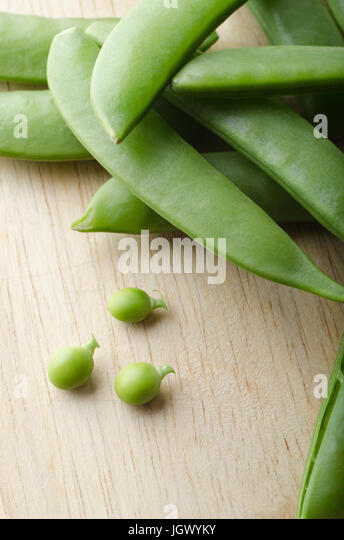 A pile of pea pods, with three tiny baby peas extracted and placed on a light wooden table.  Stalks intact. - Stock Image