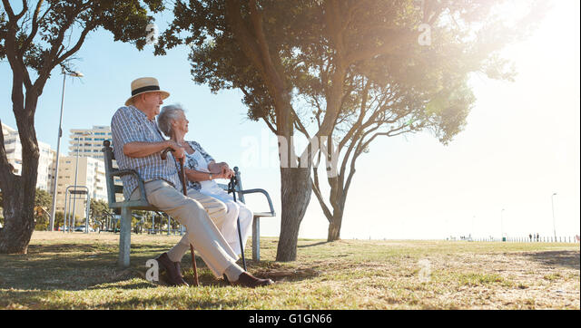 Full length outdoor shot of senior couple sitting on a bench on a summer day. Retired man and woman relaxing outdoors. - Stock Image