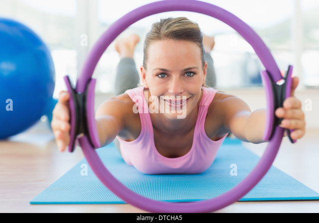 Sporty woman with exercise ring in fitness studio - Stock-Bilder