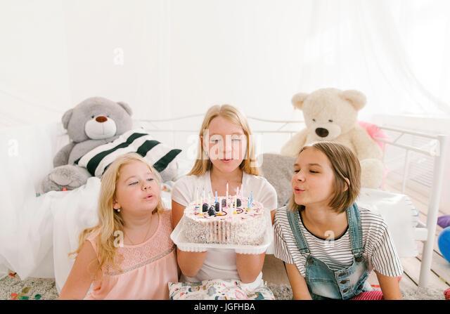 Middle Eastern sisters extinguishing candles on birthday cake - Stock Image