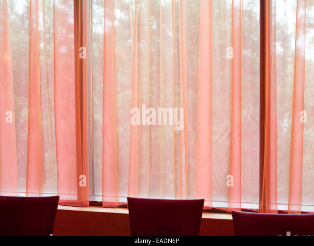 Pink curtains and red chairs of dining room - Stock Image