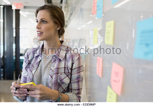 Businesswoman writing adhesive notes on whiteboard - Stock-Bilder