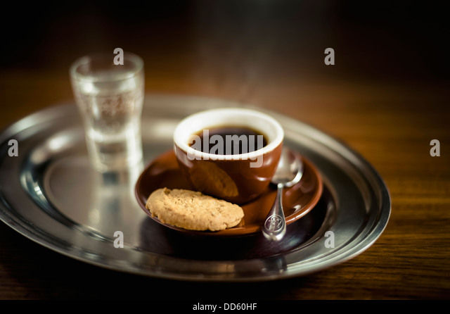 Espresso black coffee with cookie and glass of water on tray - Stock Image