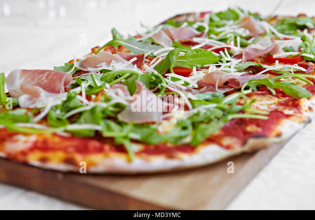 Fresh pizza with rocket and parma ham on chopping board - Stock Image