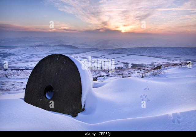 The last rays of sun on the snow and millstones of Stanage Edge, Derbyshire, England, United Kingdom, Europe - Stock Image