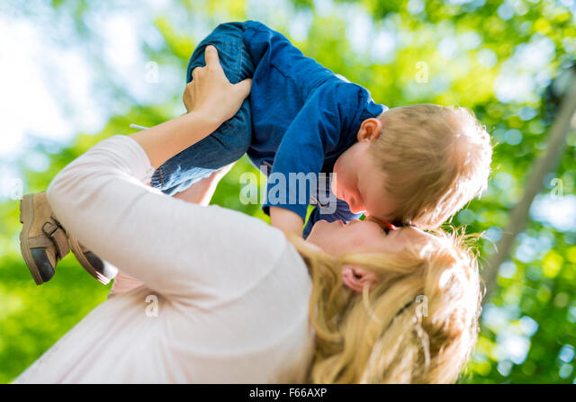 Beautiful young mother playing and smiling with her handsome little son - Stock Image