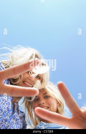 Sisters making peace sign together - Stock-Bilder