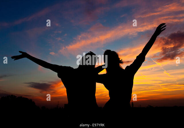 Young women with arms raised dancing at sunset - Stock Image