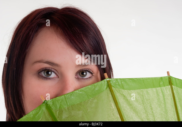 portrait of beautiful teenage girl with green umbrella - Stock Image