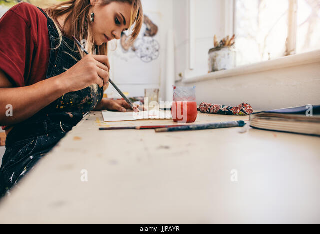 Image of beautiful woman drawing pictures in her workshop. Female artist painting in her studio. - Stock Image