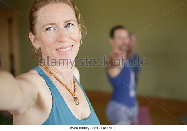 Mature female practicing yoga indoors - Stock Image