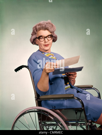 1960s SENIOR WOMAN WEARING GLASSES SITTING IN WHEELCHAIR READING LETTER INSURANCE CHECK HEALTHCARE PATIENT - Stock Image