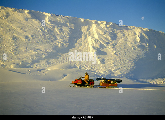 New Zealand field worker on Skidoo on fast ice Terminal face of Erebus Glacier Tongue Moon Spring McMurdo Sound - Stock Image