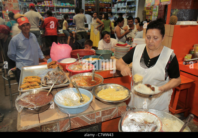 Managua Nicaragua Mercado Roberto Huembes market marketplace shopping vendor stall Hispanic woman man cook customer - Stock Image