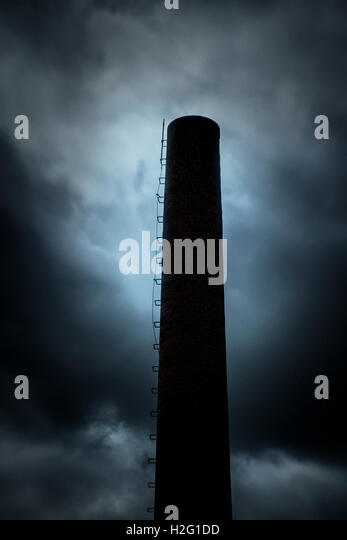 Dark and ominous sky and silhouette of factory chimney. Heavy clouds and darkness. Moody and scary setting in industrial - Stock-Bilder