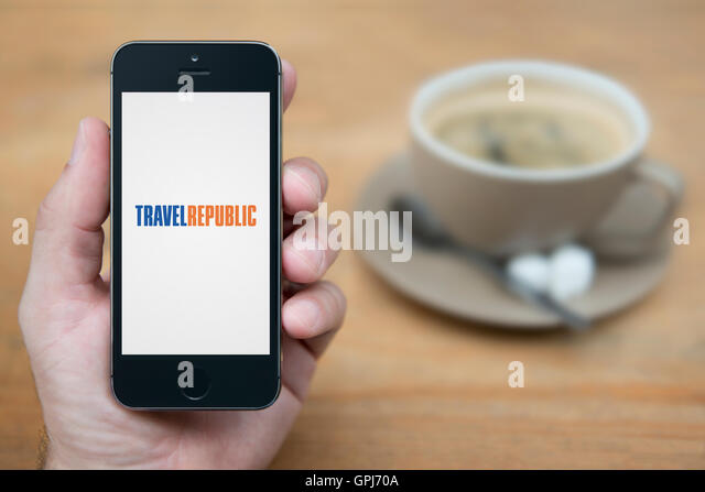 A man looks at his iPhone which displays the Travel Republic logo, while sat with a cup of coffee (Editorial use - Stock-Bilder