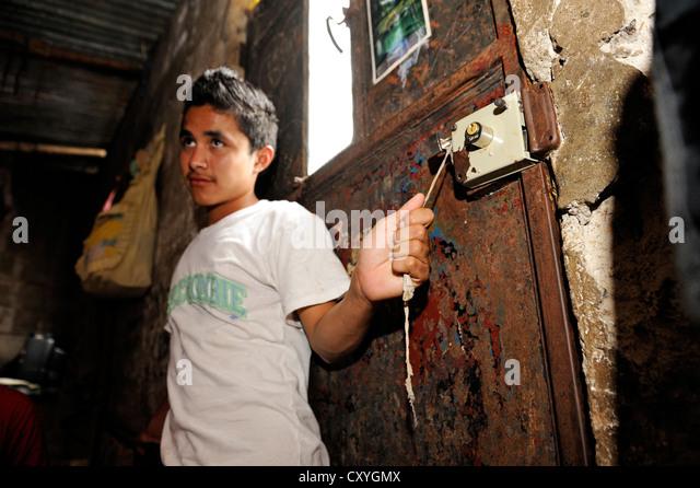 Teenager, 16 years old, at home in his humble hut, Lomas de Santa Faz slum, Guatemala City, Guatemala, Central America - Stock Image