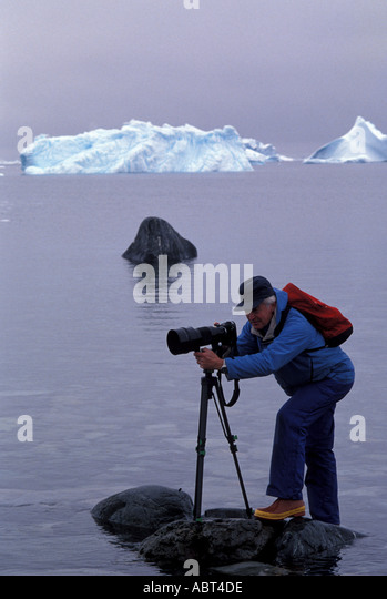 ANTARCTICA Photographer standing on rock surrounded by ice - Stock Image