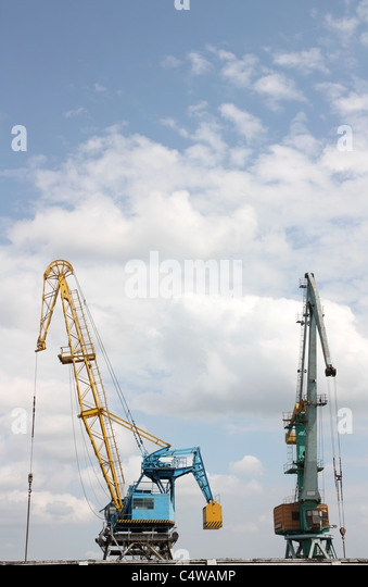 Two elevating cranes in river port against the sky - Stock Image