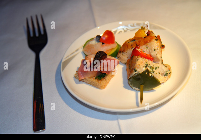 China Beijing Air China airlines onboard meal food kabob skewered meat chicken peppers fork plate service - Stock Image