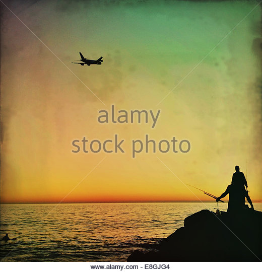 Airplane above fishermen - Stock Image