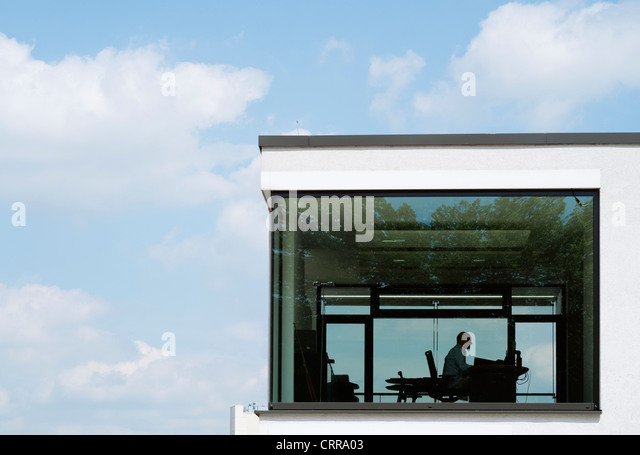 Man working in office in modern commercial and residential upmarket property development in Rheinauhafen Cologne - Stock Image