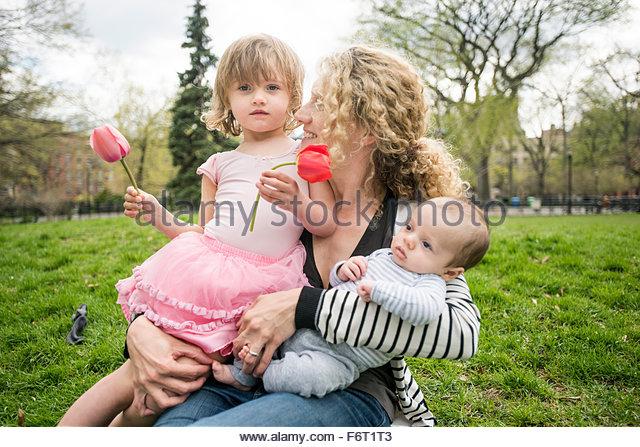 Mother and children sitting in grass - Stock-Bilder