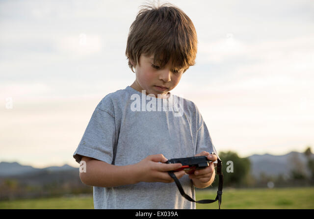 Boy looking at digital camera in park - Stock Image