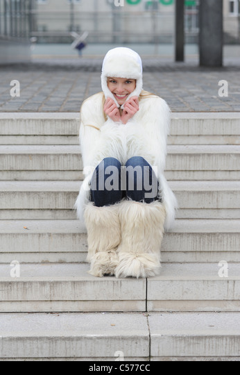 Woman wearing winter clothes on steps - Stock Image