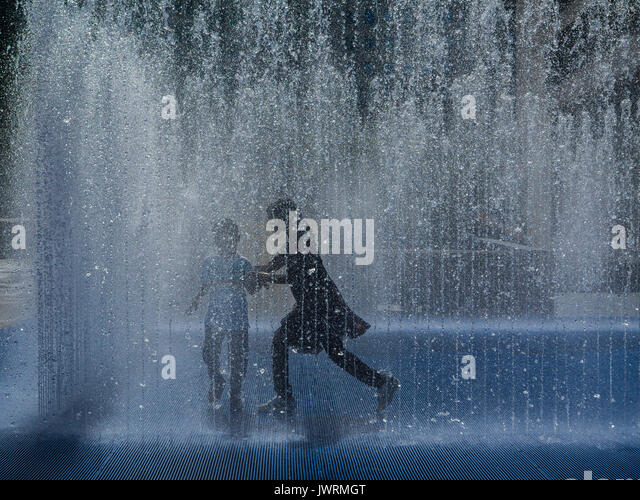 Playing in fountains on London's South Bank embankment - Stock Image